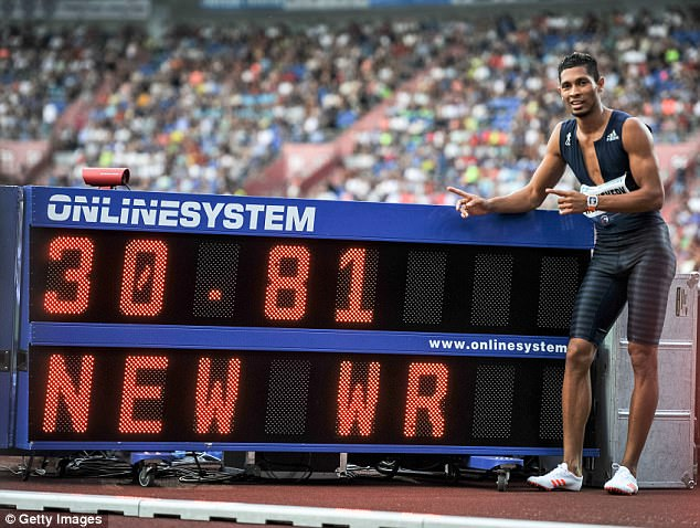 Wayde Van Niekerk posing by the record board